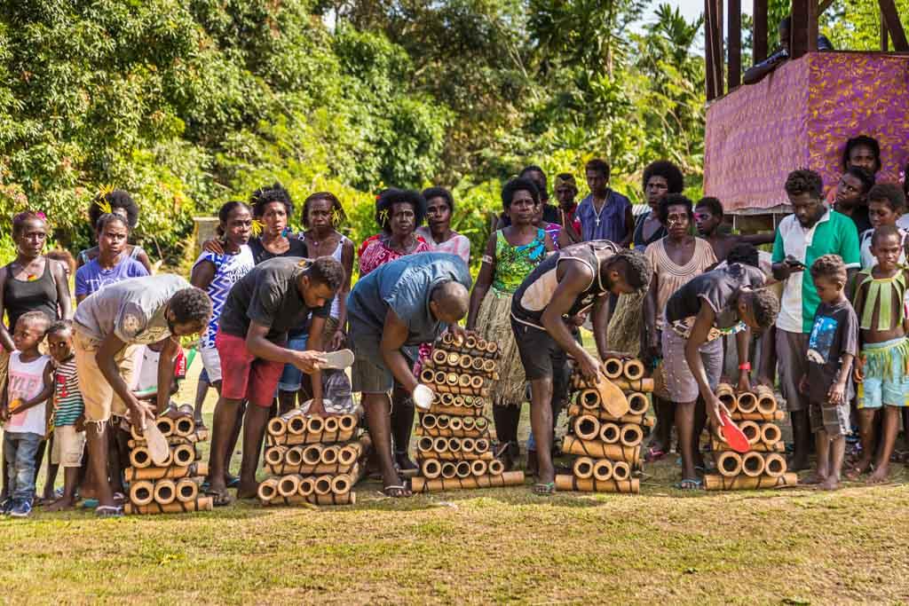 In einer Bamboo-Band werden verschieden lange Bambusrohre rhythmisch mit Flop-Flop-Sohlen angeschlagen / © FrontRowSociety.net, Foto: Georg Berg