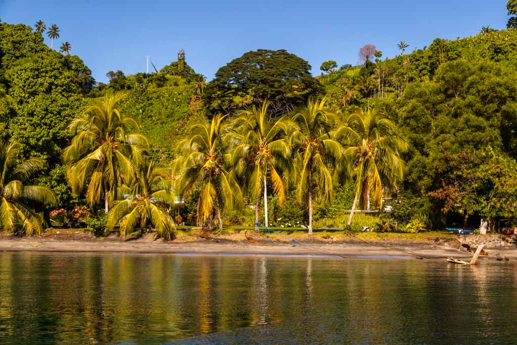 Individual palm trees and house ruins are testimonies to the magnificent beach promenade of Kieta. The wealthy employees of the inland Panguna copper mine resided here / © FrontRowSociety.net, photo: Georg Berg