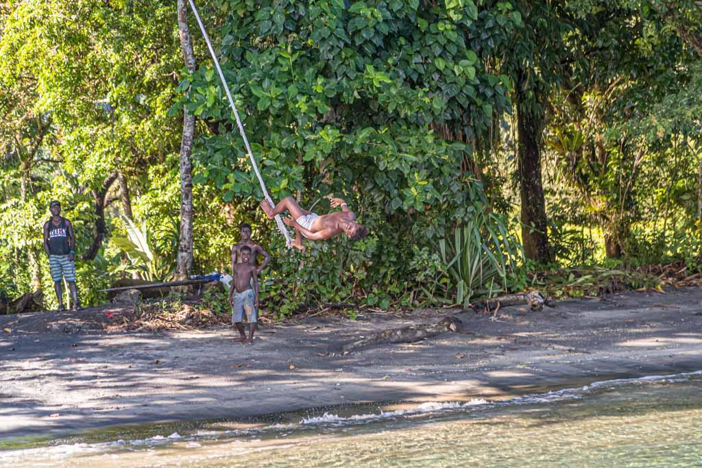 Mit Improvisationstalent und einem im Strandgut gefundenen Schiffstau überbieten sich die Jugendlichen beim kunstvollen Sprung ins Wasser / © FrontRowSociety.net, Foto: Georg Berg