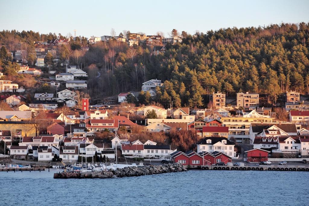 An den Ufern des Oslofjords fügen sich typisch skandinavische Holzhäuschen in rot und weiß harmonisch in die waldreiche Landschaft
