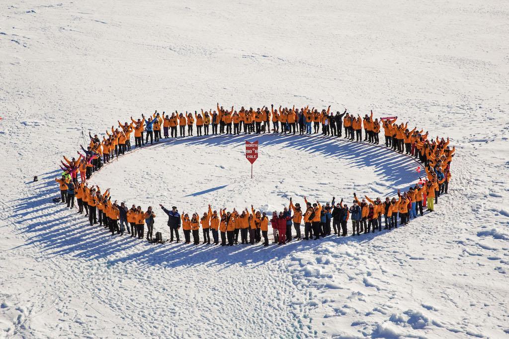 Crew und Passagiere der Expedition bilden einen Kreis um den Nordpol herum