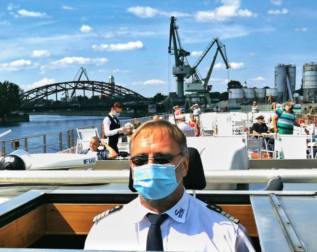 Vorschriftsmäßig mit Maske: Kapitän Peter Grunewald im abgesenkten Steuerhaus / © FrontRowSociety.net, Foto: Dr. Peer Schmidt-Walther