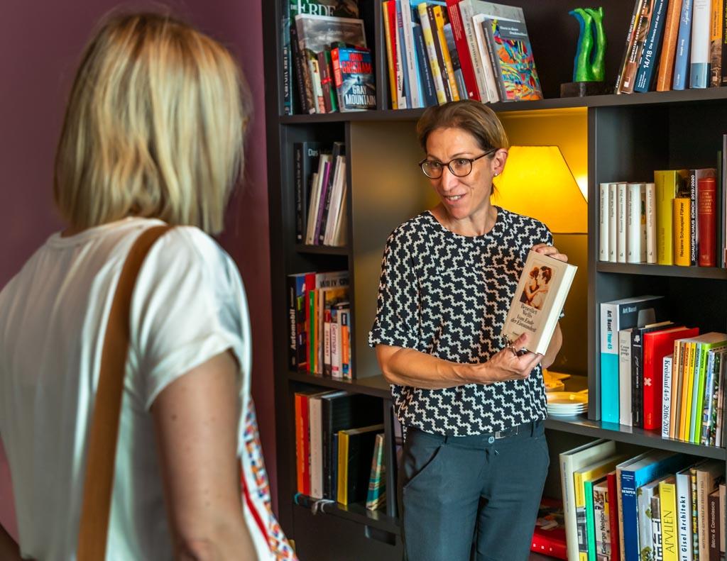 Die kleine Bibliothek führt ausschließlich Bücher von Schriftstellern, die schon mal im Haus zu Gast waren. Sie hinterließen ihre Werke meist signiert. Hoteldirektorin Isabelle Zeyssolff zeigt einige Werke / © FrontRowSociety.net, Foto: Georg Berg
