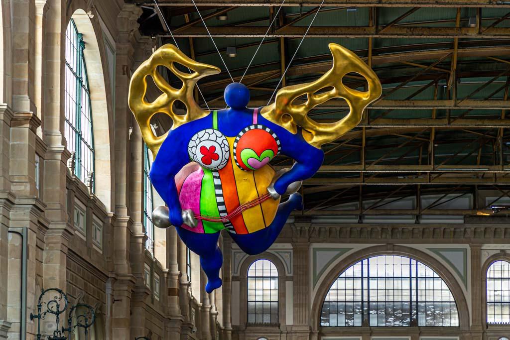 Der mollige Blaue Engel von Niki de Saint Phalle in Zürichs ältestem Bahnhof ist Treffpunkt der Food Tour namens Swiss Classics / © FrontRowSociety.net, Foto: Georg Berg