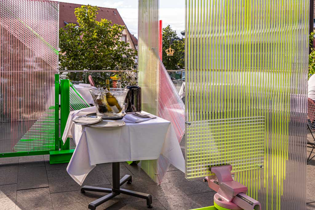 Kunst in Zeiten von Corona. Der Künstler Samuel Treindl entwarf einen Spuckschutz. Schutz und Zierde zugleich für die Terrasse im Restaurant Krone / © FrontRowSociety.net, Foto: Georg Berg