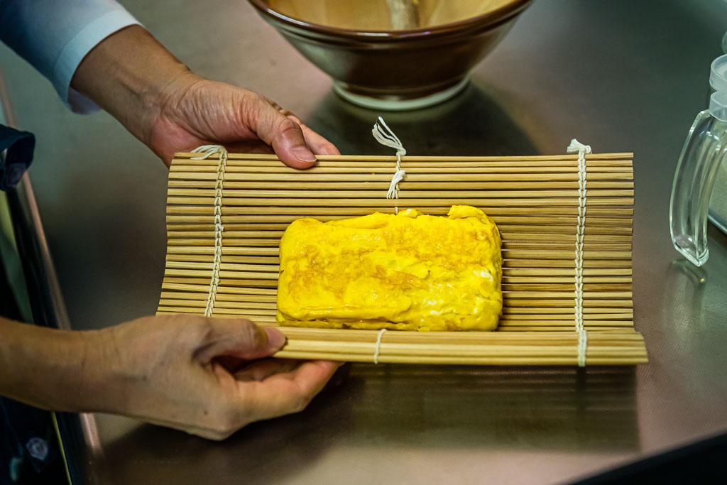 Das angebratene Omelett wird in einer Bambusmatte in Form gebracht / © FrontRowSociety.net, Foto: Georg Berg