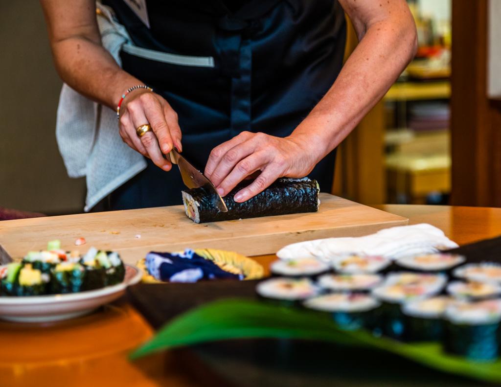 Beim Zubereiten von Futo Maki Sushi wird die glänzende Seite des Algenblatts nach unten gelegt. Nach jedem Schnitt sollte das Messer mit einem feuchten Tuch gereinigt werden, damit alle Schnitte akkurat und sauber werden / © FrontRowSociety.net, Foto: Georg Berg