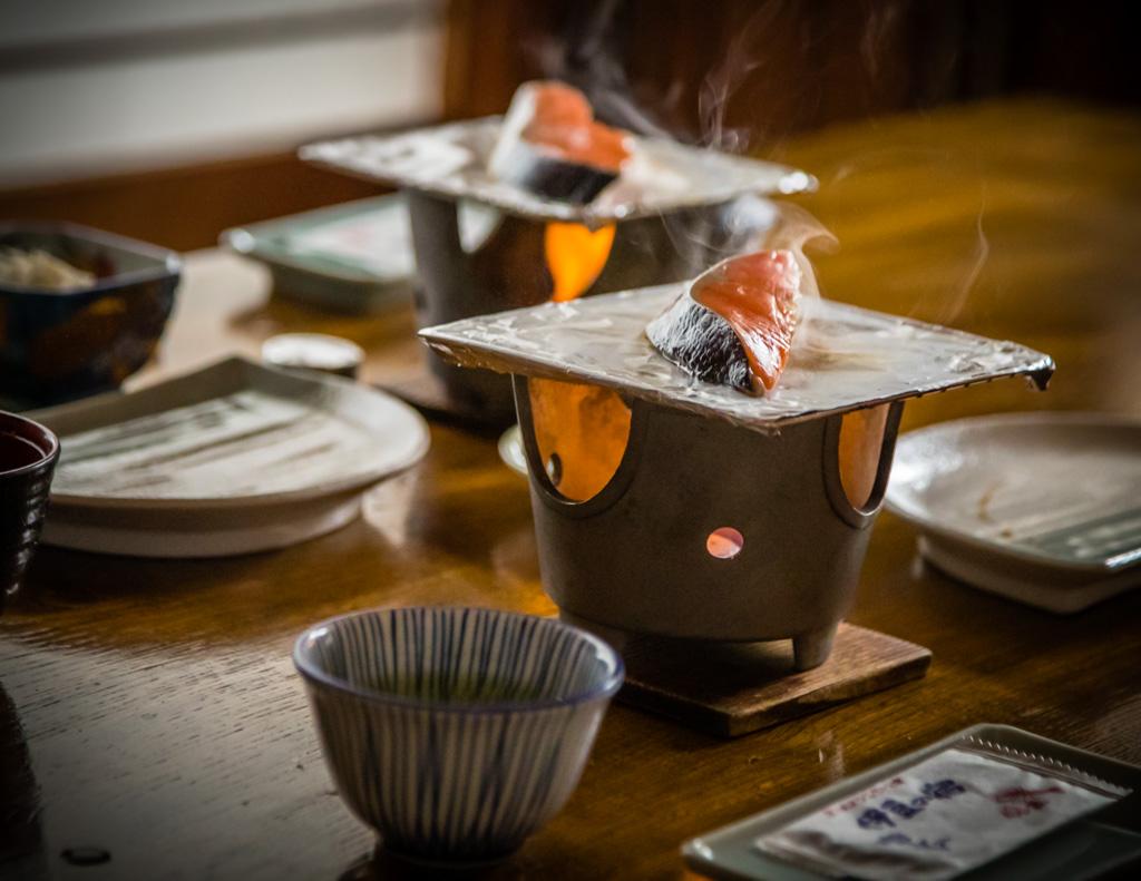 Fisch ist fester Bestandteil eines japanischen Frühstücks. Hier bereitet man ihn selber auf einer kleinen Tischfeuerstelle zu - frischer geht's kaum / © FrontRowSociety.net, Foto: Georg Berg