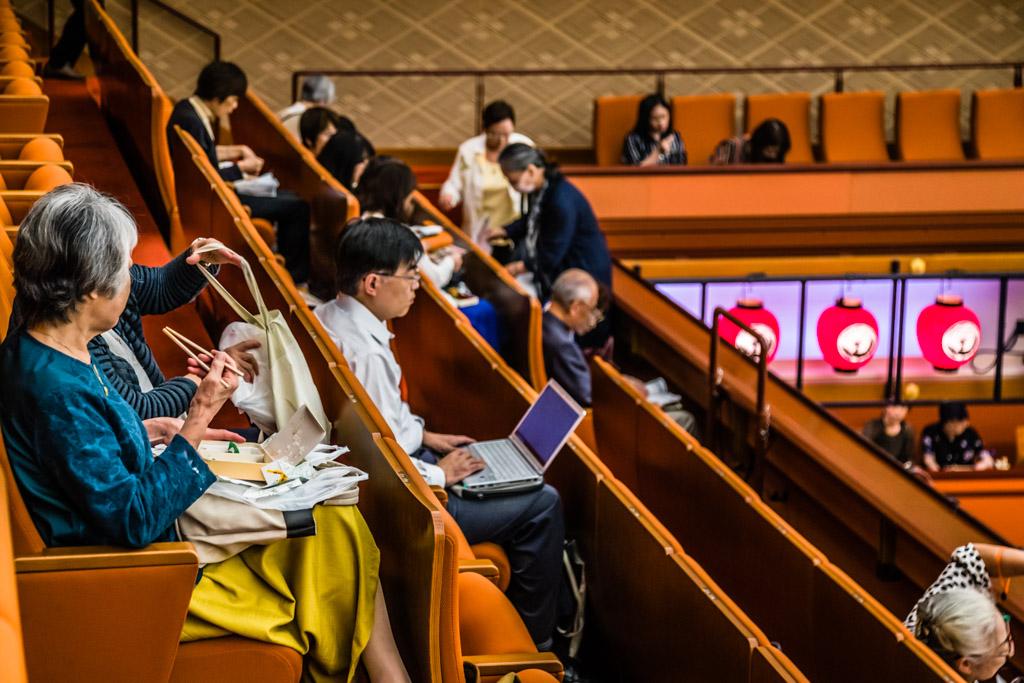Vorhang zu - Bento auf. Im Kabuki Theater in Tokio sind die Zuschauer bestens vorbereitet. Statt feiner Handtaschen führt man hier geräumige Stoffbeutel mit sich. Aber auch das Klischee des stets arbeitsamen Japaners wird beim Betrachten dieses Fotos bedient / © FrontRowSociety.net, Foto: Georg Berg