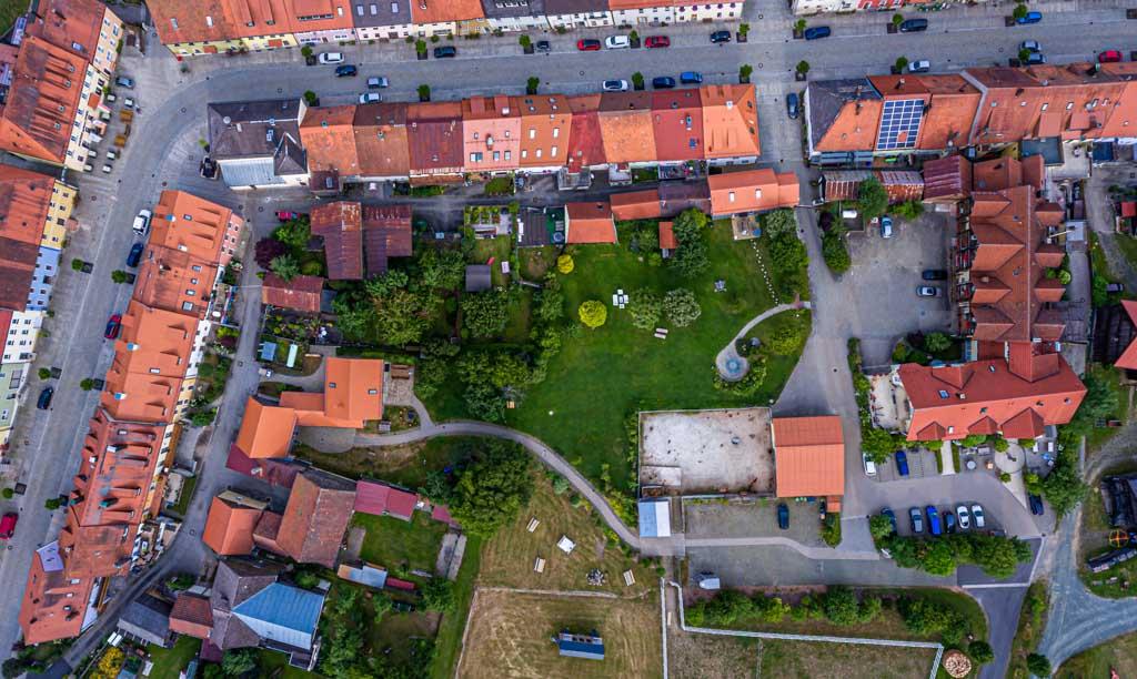 Das Luftbild verdeutlicht das Konzept der Hollerhöfe. Im Dorf verteilt befinden sich die restaurierten Häuser. Jedes Haus an der Straße hat nach hinten raus noch einen Stall oder eine Scheune durch eine kleine Gasse getrennt / © FrontRowSociety.net, Foto: Georg Berg