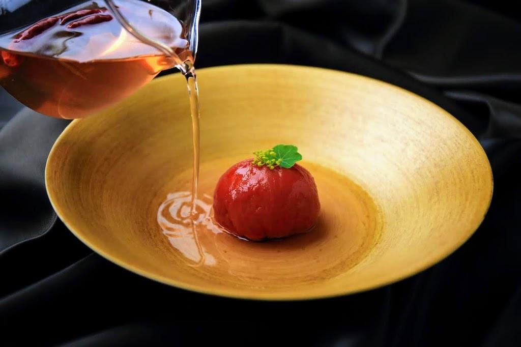 Ganze, eingelegte Tomate, angerichtet mit Kapuzinerkresse und Dillblüten