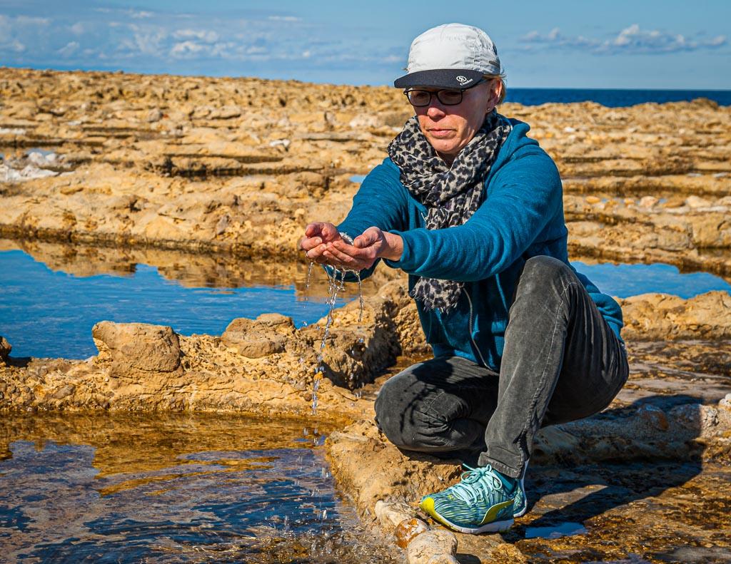 FrontRowSociety Redakteurin Angela Berg schöpft das salzhaltige Wasser aus einer antiken Salzpfanne / © FrontRowSociety.net, Foto: Georg Berg