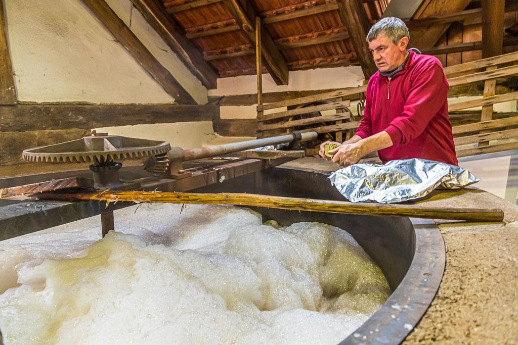 """Kurz vor dem Siedepunkt fügt Braumeister Sepp Neuber aus der Gemeinde Falkenberg Hopfen zur Stammwürze des zukünftigen Zoigl-Bieres. Das Aufkochen macht Bier zu einem """"sicheren"""" Getränk / © FrontRowSociety.net, Foto: Georg Berg"""