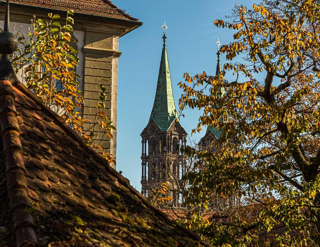 Die Türme des Bamberger Doms St. Peter und St. Georg hinter einem Kastanienbaum und anderen Gebäuden der Bergstadt Bamberg / © FrontRowSociety.net, Foto: Georg Berg