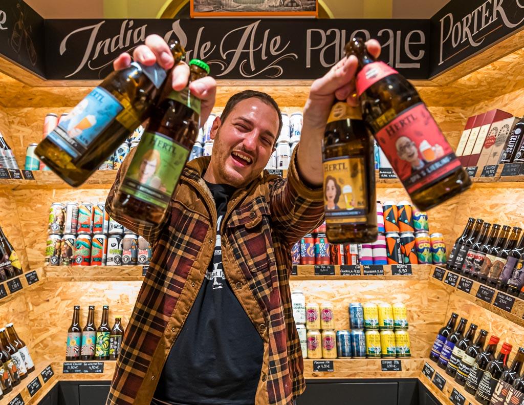 Mit großer Begeisterung bei der Sache: David Hertl mit Bier aus der eigenen Familienbrauerei und umgeben von Biersorten aus aller Welt / © FrontRowSociety.net, Foto: Georg Berg