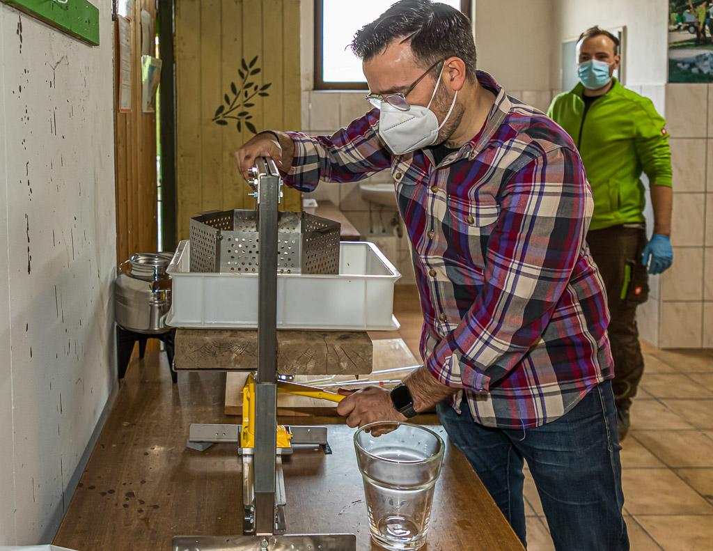 Olivenöl-Produzent Bastian Jordan an der Handpresse. Bastian Jordan richtet die Handpresse ein, aus der bis zum Ende des Tages dann 3,5 Liter Öl gewonnen werden / © FrontRowSociety.net, Foto: Georg Berg