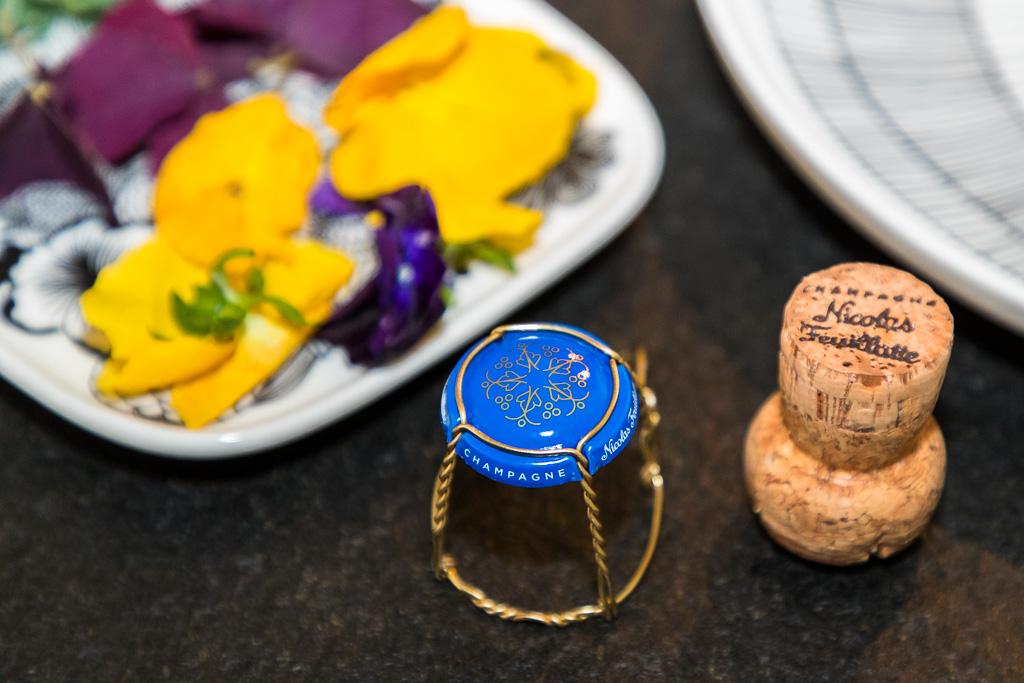 Das symbolkräftige Logo von Nicolas Feuillatte schmückt auch den Champagnerdeckel und erzählt von Weintrauben, Weinblättern, Menschen und einem Stern für die ErstklassigkeitNicotesFendtatte202Nicolas FocalCHAMPAGNE / © FrontRowSociety.net, Foto: Georg Berg
