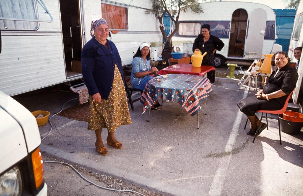 Ein aus mehreren Familien bestehender Clan hat sich auf einem Parkplatz gemeinsam eingerichtet / © FrontRowSociety.net, Foto: Georg Berg