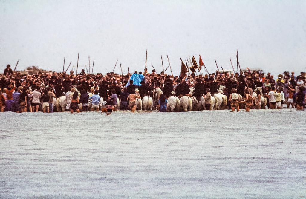 Die Gardians auf ihren Pferden bilden im Meer einen Halbkreis, in dem die Heiligenfiguren bis ins Wasser getragen werden / © FrontRowSociety.net, Foto: Georg Berg