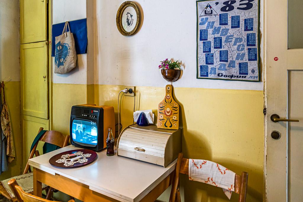 """Stoisch hört sich der gehäkelte Lenin in der Küche der """"Red Flat"""" die Dauerschleife an, mit der das bulgarische Fernsehen die Eröffnung der ersten Coca Cola Abfüllanlage des Ostblocks rühmt / © FrontRowSociety.net, Foto: Georg Berg"""