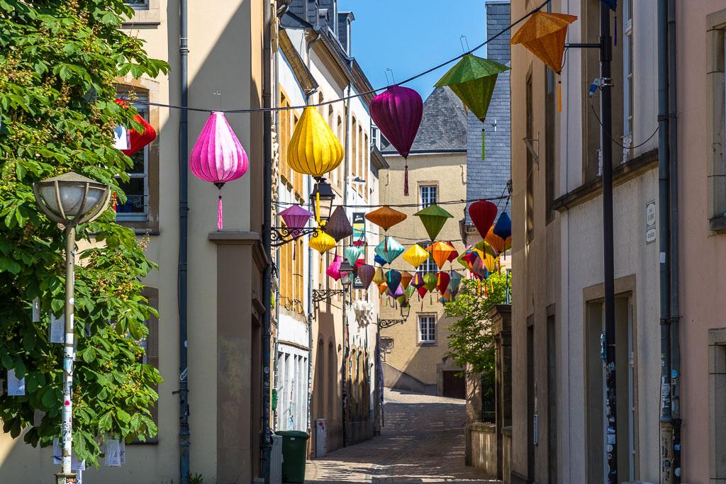 Lampions über der Straße. Auch wenn es aufgrund von Corona 2021 relativ ruhig in der Stadt ist - Luxemburg ist Sitz mehrerer EU Institutionen. Hier leben Menschen aus 170 Nationen / © FrontRowSociety.net, Foto: Georg Berg